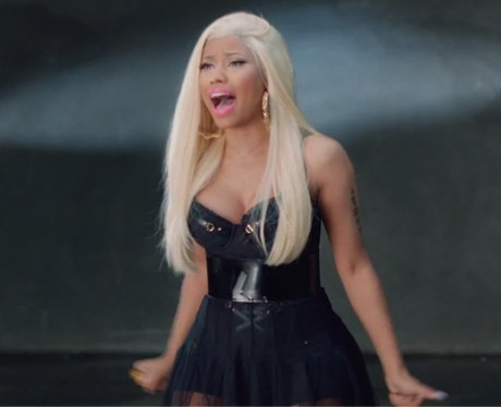 nicki wears a black corseted dress while belting out the