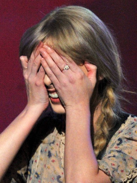 Taylor Swift covering her eyes