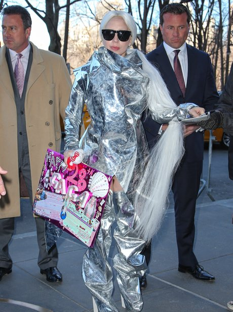 Lady Gaga wearing a foil outfit carrying a birthda